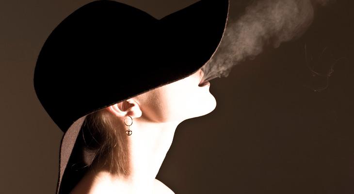 Женщина выпускает дым