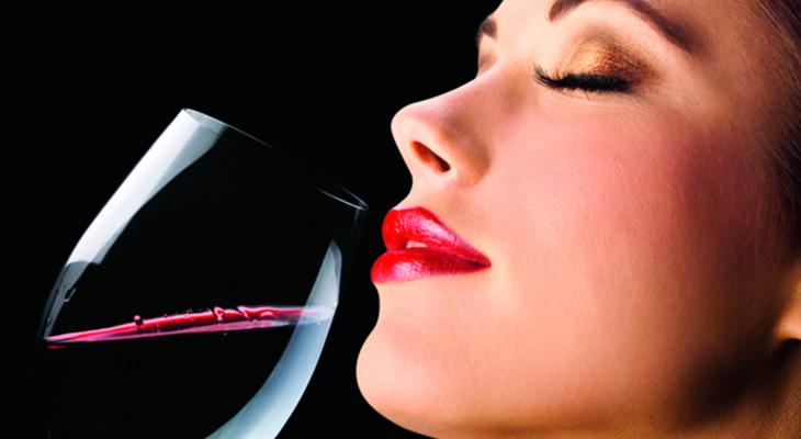 Девушка наслаждается запахом вина